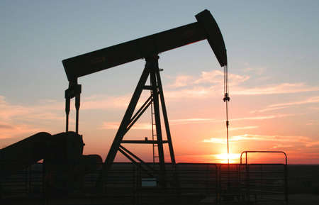 Oil field pump jack silhouette with setting sun
