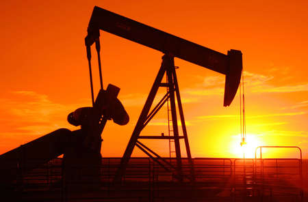 the setting sun: Oil field pump jack silhouette with setting sun