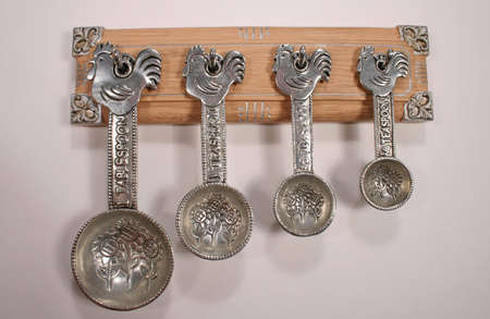 measuring spoons: Unique set of silver measuring spoons with sunflower design and rooster on the handle Stock Photo