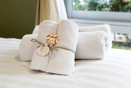 Closeup of soft white towels, rolled  folded and tied with rope and shell on bed  Stock Photo