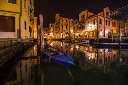 Chioggia city on the water in the evening with beautiful lights