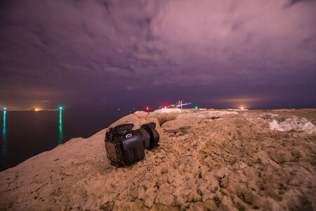 A professional camera on the sea dike at night