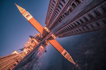 Campanile di San Marco in Venice is reflected in a puddle Фото со стока