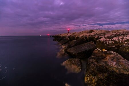Red lighthouse at night with the light on the dam on the sea