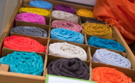 Many colored scarves for sale in the shop in a wooden cabinet Stockfoto