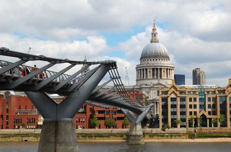 View of St Paul Cathedral and the Millennium Bridge with a cloudy sky photo