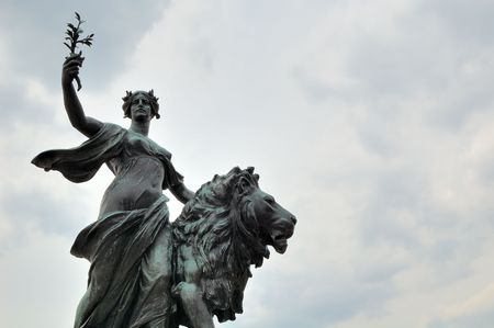 Bronze statue of a young woman raising her arm with a lion by her side photo