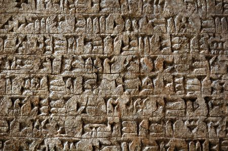 Ancient sumerian cuneiform writing engraved in a stone photo