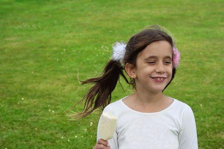 Beautiful girl eating an ice cream in a green field Stock Photo - 5282145