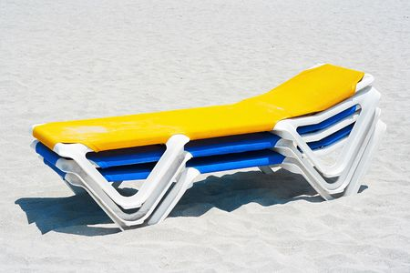 A stack of yellow and blue beach chairs in the sand photo