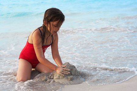 kids playing water: Beautiful caucasian girl building a sand castle in the beach Stock Photo