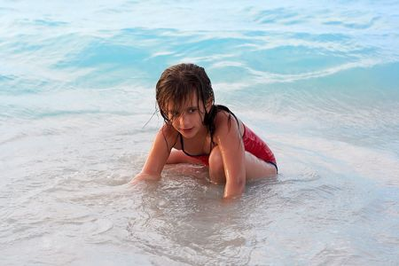 Beautiful caucasian girl sitting in the beach with a mischievous look photo