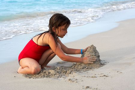 Beautiful caucasian girl building a sand castle in the beach photo