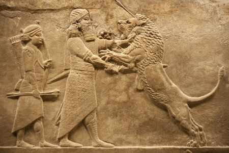 babylonian: Old relief representing an assirian warrior hunting lions Stock Photo