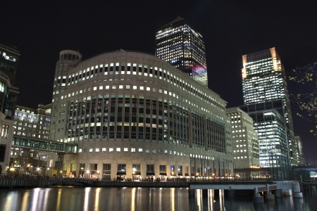 Canary Wharf skyscrapers in London at night with reflections in the river photo