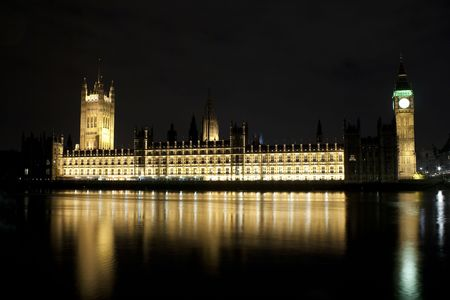 The Big Ben and the Parliament illuminated at night with reflections in the river photo