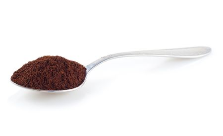 Shiny silver spoon filled with coffee on a white background photo