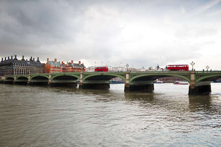 Westminster Bridge in London with red double decker buses in a cloudy day photo