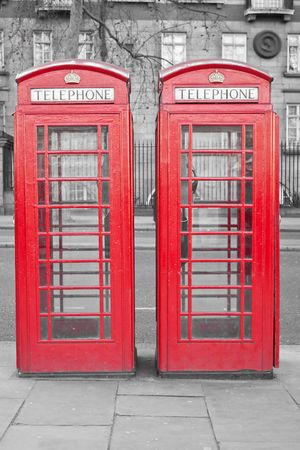 english famous: Two typical London bright red phone cabins with a desaturated background Stock Photo