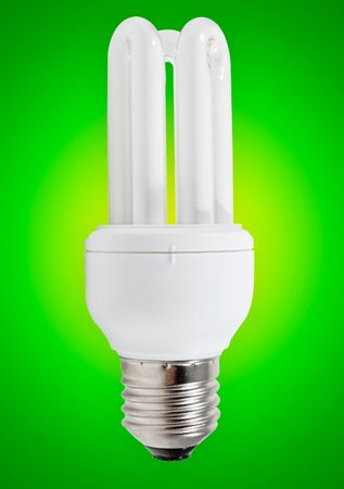 Energy saving bulb on a green background photo