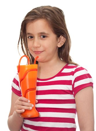 Small girl drinking soda from a funny orange vase on a white background photo