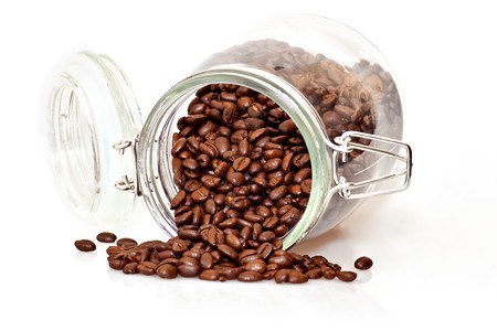 Coffee beans spilling out of a cristal jar on a white background photo