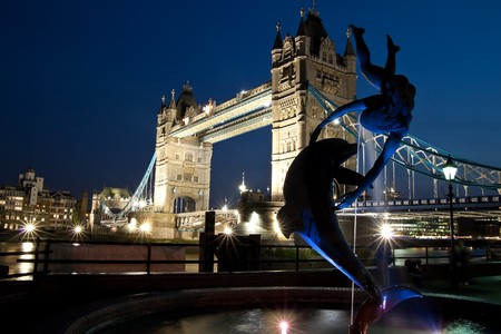 Night view of the Tower Bridge in London with a sculpture in the foreground photo