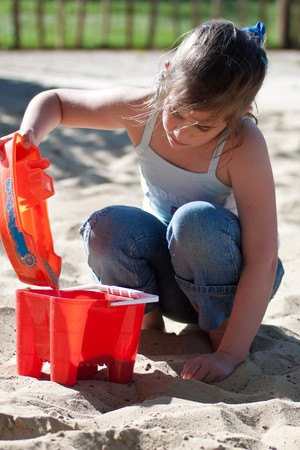 sand pit: Girl playing in a sand pit in a beautiful summer day Stock Photo