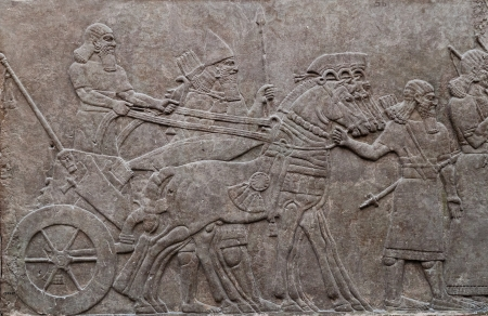babylonian: Relief of ancient assyrian warriors in a horse drawn chariot