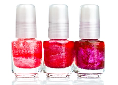 Nail polish bottles in shades of red on a white background with reflections photo