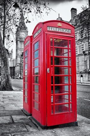 A pair of traditional red phone booths in London with the Big Ben in a desaturated background photo