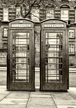 Black and white image of two traditional London phone booths photo