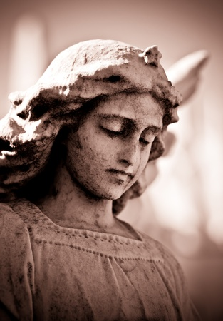 angel cemetery: Weathered young angel in sepia tones