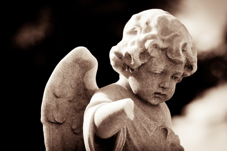 Weathered child angel statue in sepia tones photo
