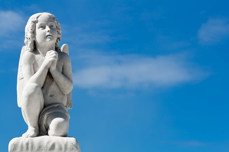 Praying angel with a blue sky background