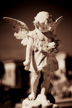 Child angel statue in a cemetery in sepia tones photo