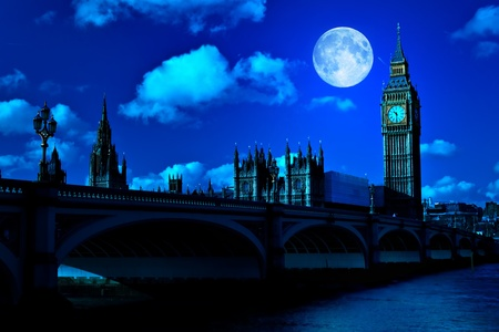 Midnight picture of the Big Ben and Westminster Bridge in London with a full moon photo