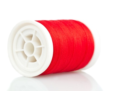 Reel with red thread on a white background photo