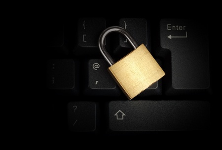 Brass closed padlock on a black keyboard Stock Photo - 9383896