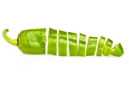 Green chili pepper cut in pieces on a white background photo