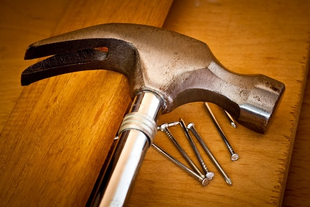 Hammer and nails on a wood background photo