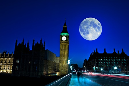 Night scene in London showing the Big Ben, a full moon and traffic on Westminster bridge photo
