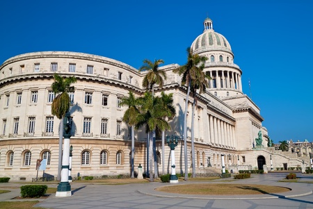 Landscape view of the Capitol building ( El Capitolio )  in Havana with a beautiful blue sky and royal palm trees photo