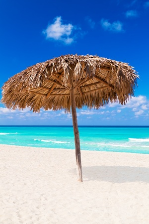 Thatched umbrella on a sandy tropical beach Stock Photo