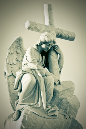 angel statue: Grunge image of a sad angel holding a cross in greenish shades Stock Photo