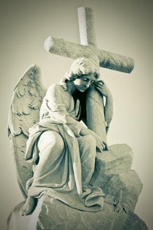 christian angel: Imagen de grunge de un �ngel triste con una Cruz en tonos verdosos Foto de archivo