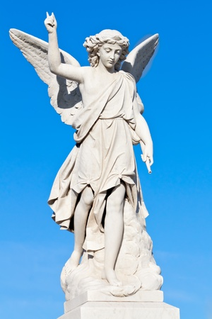 Marble statue of a young angel with a blue sky background