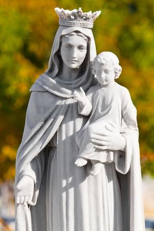 madona: Estatua de la Virgen con un ni�o con un fondo de vegetaci�n difusa de coronado Foto de archivo