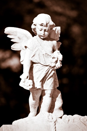 Statue of an infant angel in sepia shades Stock Photo - 9397251