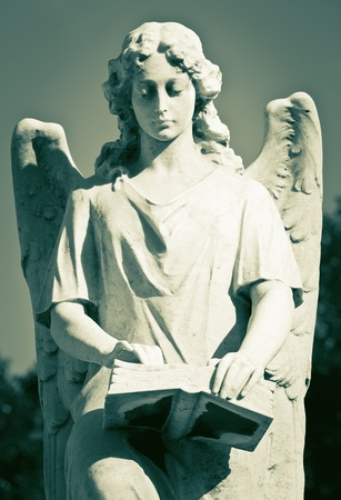 religious angel: Statue of a beautiful female angel holding a book in greenish shades Stock Photo